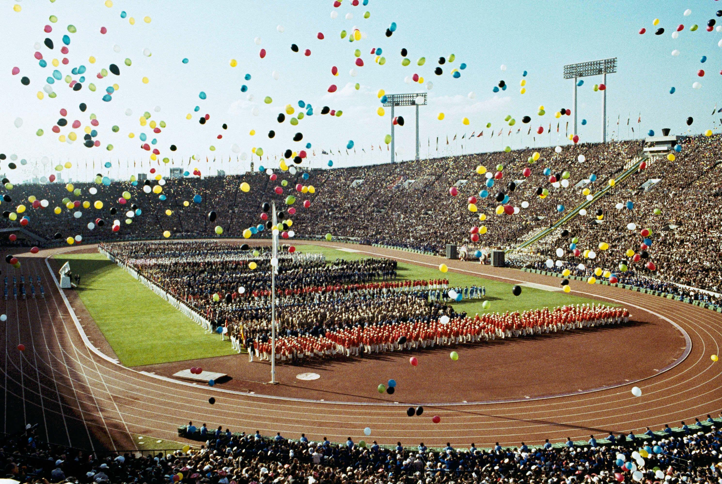 1964年夏季奧運會在東京國家體育場舉行的開幕式上,氣球飛過奧運選手和觀眾。(檔案照片/美聯社)
