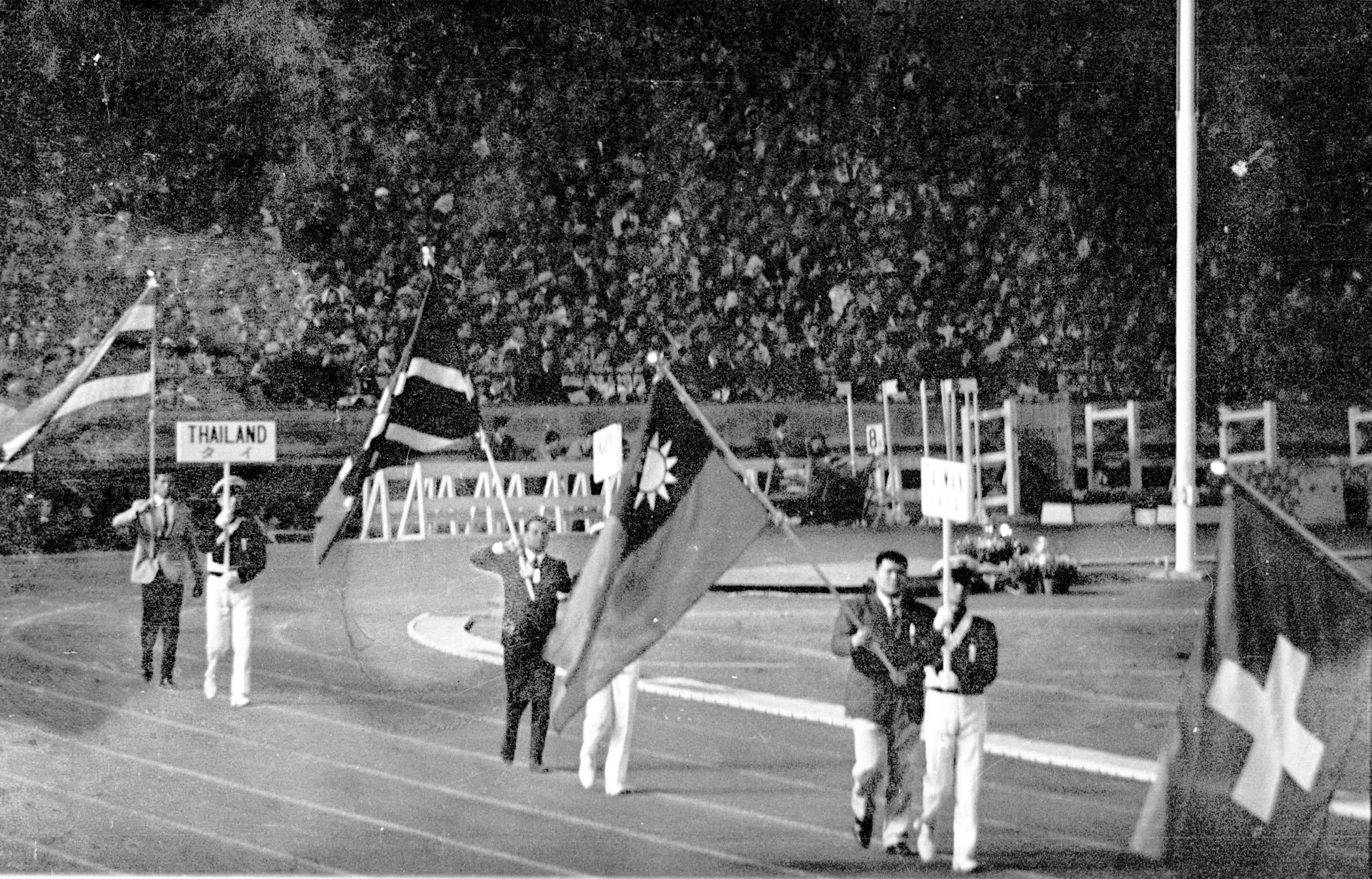 1964年東京奧運,中華民國以「台灣」(TAIWAN中華民國)的名義參加。圖為東奧閉幕典禮上,柔道選手張照輝(前右2)手持青天白日滿地紅國旗入場。(中央社檔案照片)