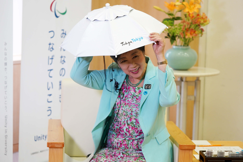 小池百合子在專訪中親自戴上抗熱傘帽,推銷東京炎夏的去暑良方。(中央社記者吳家昇攝)