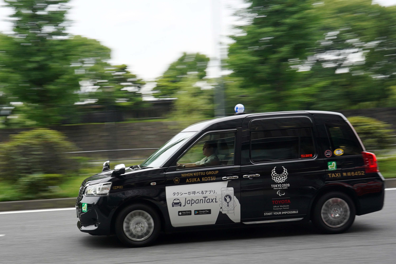 日本為奧運推出的新款計程車,車體色彩以有悠久歷史的「深藍」為底,後門貼上白色奧運徽章。(中央社記者吳家昇攝)